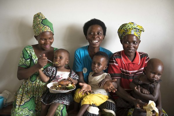 Mothers in Rwanda feed their children with a bio-fortified sweet potato puree.